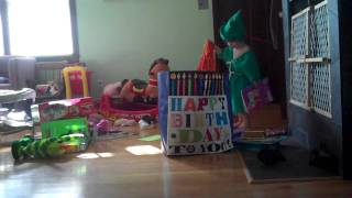 Toddler Peruses Presents in Peter Pan Costume