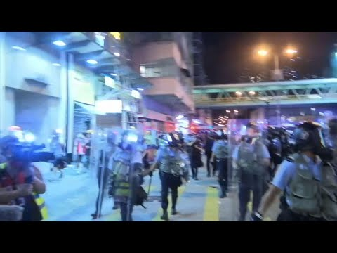 Hong Kong police armed with riot shields and batons marched down streets and fired tear gas at a group of pro-democracy protesters rallying outside a police station in the crowded urban neighborhood of Sham Shui Po. (Aug. 14)
