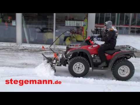 ATV mit einem Schneeschild beim Schnee schieben im Winter 2009