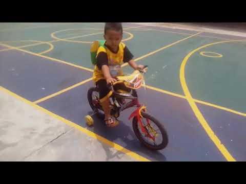 Adik Aik baru tahu naik sepeda roda 4, main di lapangan SMP UMMA.