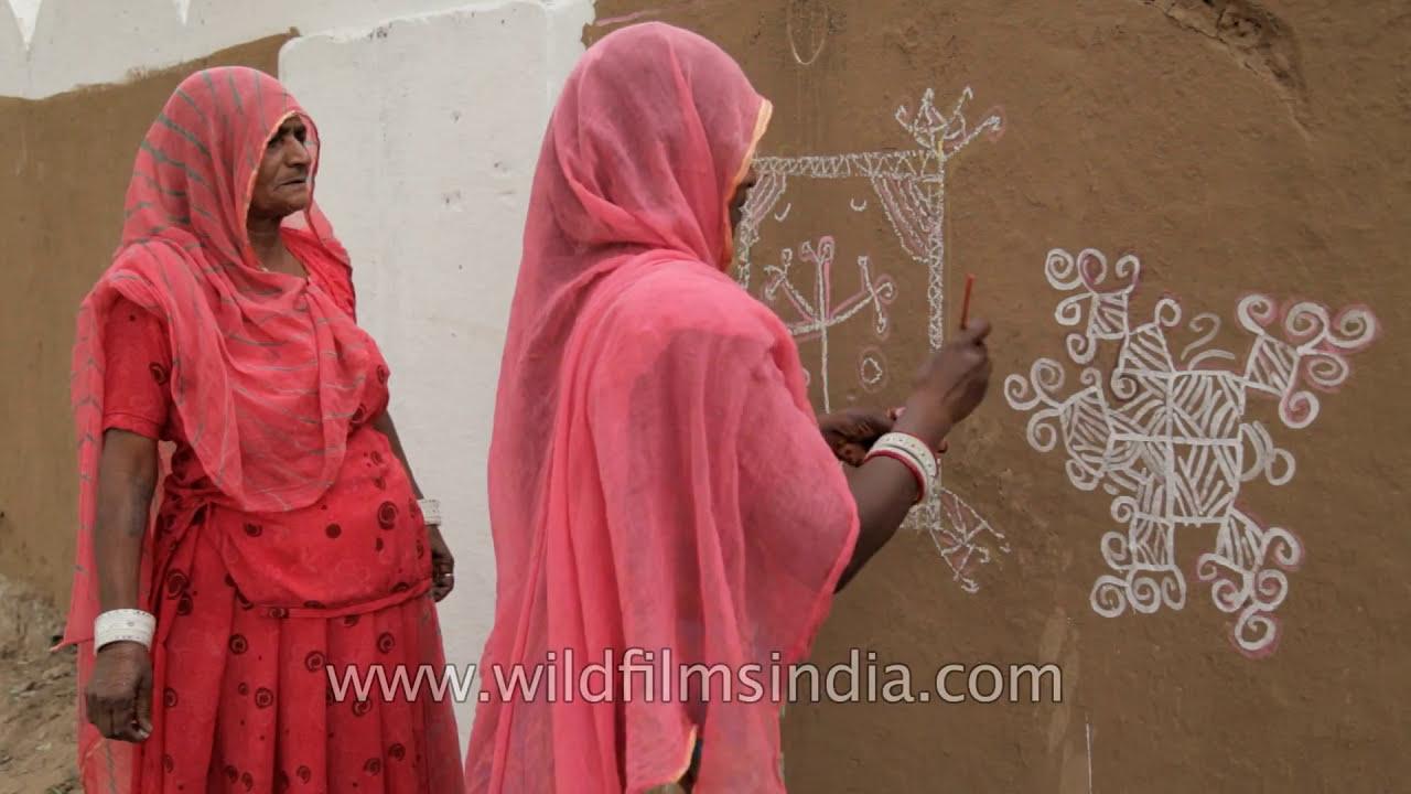 mandana wall art being painted by rajasthani woman