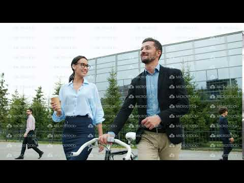 Businessman and businesswoman talking walking from work, guy is holding bike