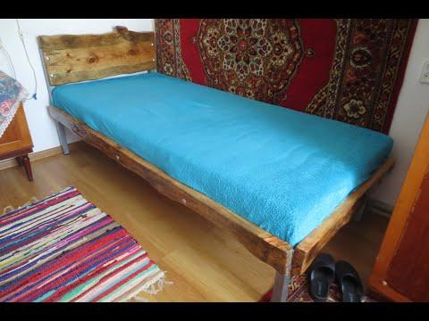 Einfaches Einzelbett aus Metall mit Holzverkleidung