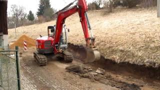 Bagr tahá z cesty ocelové roury. Excavator pulls steel pipes from the road..wmv