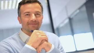 Video-Thumbnail von Werbespot: zufrieden lächelnder Energiemanager schaut dem Betrachter entgegen