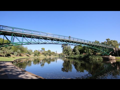 Footy players kick across Torrens River