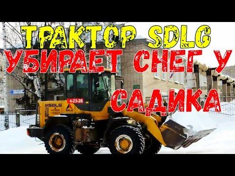 Трактор SDLG убирает снег у садика