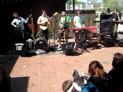 "Mumford and Sons playing their famous ""The Cave"", before it was famous, outside a Pizzeria"