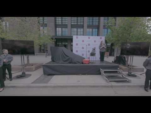 A stage outside with a race car under a sheet