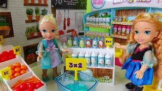 Elsa and Anna toddlers go shopping at the supermarket and buy toys