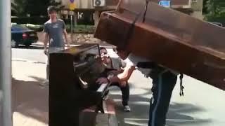 Грузчик играет с пианино на спине