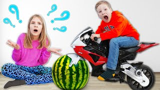 Amelia and Akim play with watermelon and toys in the garden