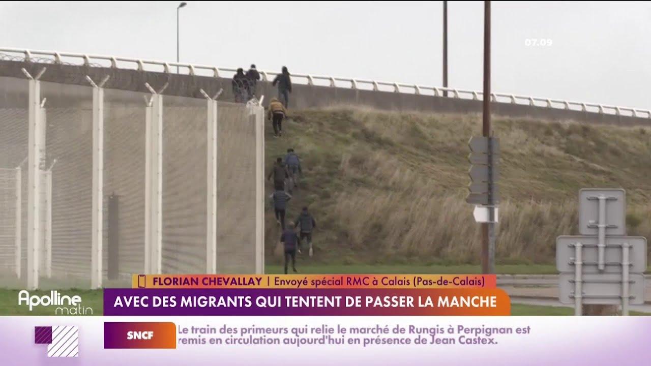 Un groupe de migrants ouvrent et sautent dans un poids lourd en mouvement.