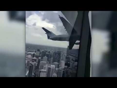 People inside a Sydney skyscraper film a low flying, approaching plane...