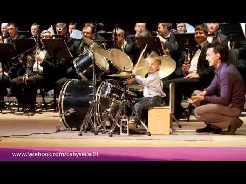 Dreijähriger dirigiert mit Schlagzeug ein Orchester