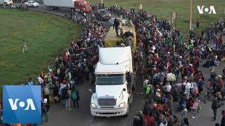 Migrants climb onto trucks as they travel across Mexico