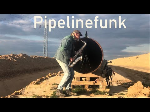 Guy playing saxophone in front of a pipeline, using its echo.