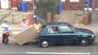 Смотреть онлайн Люди пытаются засунуть диван в машину