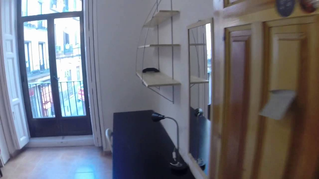 Inviting room with shelving in 8-bedroom apartment, Lavapiés