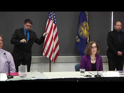 Governor Kate Brown presenting at the June 12th press conference with two sign language interpretors in the background