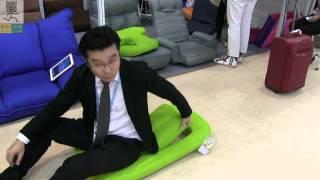 Веселый китаец демонстрирует работу кресла за 16$ на выставке в Китае