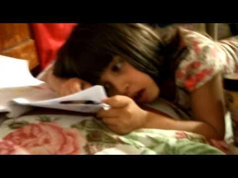 Nena haciendo la tarea en la cama