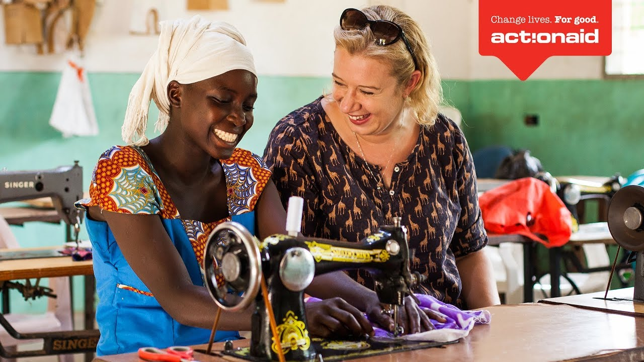 Helen from ActionAid UK talking with a young mum at her sewing machine at an ActionAid-funded women's resource centre in Kilifi county, Kenya