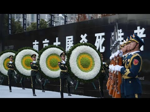 Guard of honor presents flowers during memorial ceremony for Nanjing Massacre victims