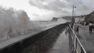 Spectator Gets Drenched As Huge Wave Breaks Over Sea Wall At Teignmouth in Devon