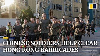 Chinese soldiers and residents help clear streets after a week of intense protest in Hong Kong