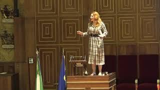 In piedi sul leggìo in Aula Magna, Università di Padova / Gabriella Greison declama Baudleaire