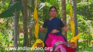 Woman in half sari swinging on an Oonjal