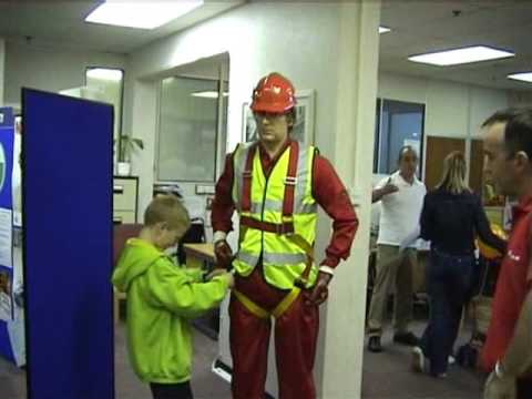 mannequin-man performming as a Living Mannequin: Fall arrest harness being put onto mannequin man by member of the public at a Safety clothing and PPE exhibition by ARCO at family open day at BAE (British Aerospace Engineering) systems in Rochester #4 (flash) for Arco on 06/07/2002