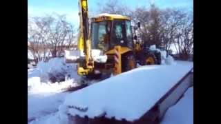 Универсальный экскаватор погрузчик JCB 4CX убирает во дворе жилого дома снег