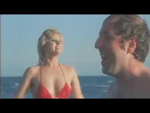 #  Carmen Villani corre verso il mare in slip rosso caldo.