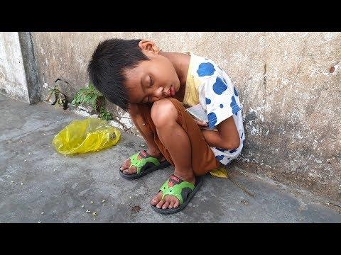 Cậu bé bán vé số ngồi ngủ gục một cách ngon lành trên đường