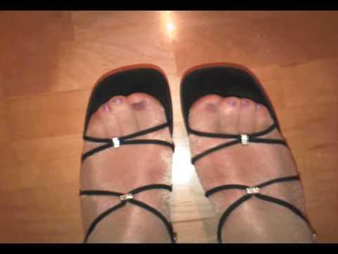 Schwarze Sandaletten und Füße