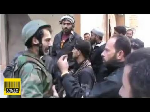Syrian soldier Mustafa Shaddoud puts down rifle to talk to his FSA