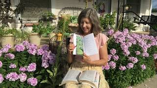 A butterfly lands on the book as Jean Ann Shirey reads Granny's Garden, pages 49 and 35.