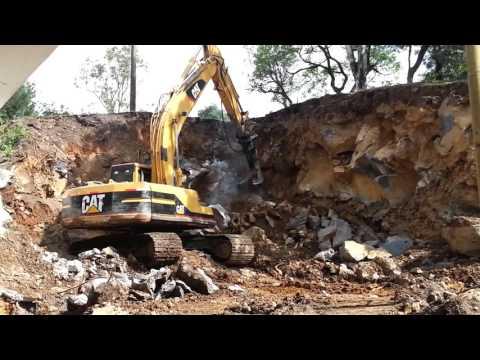 Excavadora  CAT martillo hidraulico junto a puente