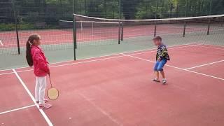 Оля и Саша играют в бадминтон. Дети забавно и смешно играют в спортивную игру. Video hd.