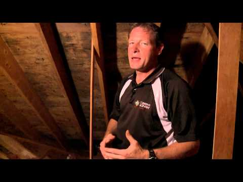 "Welcome to the 70th episode of ""On the Job""! In this episode, Larry Janesky, owner and founder of Dr. Energy Saver, takes us to the attic of a colonial home in Newtown, CT to speak about mold in the attic. Mold problems are quite prevalent in many conventionally insulated, unconditioned attics in the northeast – and in virtually any area of the country where winters are cold and houses are heated. In this particular home in Newtown, the problem is so widespread that it is possible to see the dark mold stains all over the wooden surfaces. Such a wide infestation may eventually cause wood decay and compromise the structural integrity of the roof, but it also raises serious health concerns for the family living in that home. What causes mold problems in the attic? As Larry will show, the problem begins with lack of proper air sealing. Heated air – the air that you pay to heat your home – rises and leaks into the unconditioned attic through all types of gaps, such as holes around pipes and wires, canned lights, unsealed attic hatches, and bathroom fans that vent into the attic instead of the outside. During the winter, an unconditioned attic is usually just as cold as the outside, and so are the roof and wooden structures. When heated, humid air infiltrates the freezing cold attic, it will cool down and  per each degree it is cooled, relative humidity rises 2.2%, often bringing the RH levels in the attic up to 100%, at which point condensation occurs all over the cold surfaces.The wood will soak the moisture and create the perfect conditions for mold to develop.In this particular attic, the condensation problem is so significant that the nails used to secure the roof shingles began to rust and drip all over the attic.  The only effective way to stop mold from developing in the attic is to properly seal all the gaps and holes. This will help to keep heated air in the conditioned areas from escaping into the cold attic.As it happened in this home, most builders and the typical insulation contact or will not air seal the attic before installing the insulation. That is malpractice because even if R-values are up to recommendations, common attic insulation materials such as fiberglass bats, blown fiberglass or blown cellulose, will only prevent heat from the ceiling from transferring to the attic. It will not stop air flow. Air will leak right through the insulation. An energy efficient attic is the most important component of an energy efficient home. If your home has mold in the attic or if your heating and cooling bills are too high or even if you worry that your attic is not properly insulated visit our website or give us a call to schedule a free evaluation and estimate."