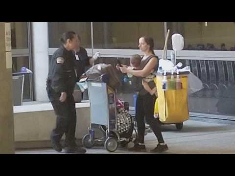 Lax airport police helping  out a woman with a baby