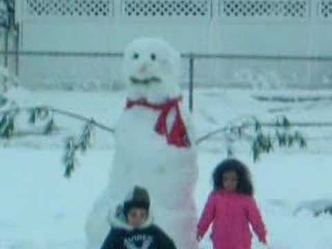 Twins playing with snowman
