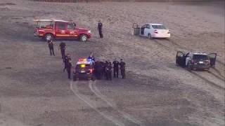 Man taken into custody after fleeing police on beach, jumping into ocean