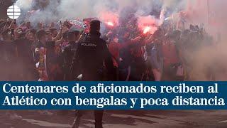 Varios centenares de aficionados reciben al Atlético con bengalas y poca distancia