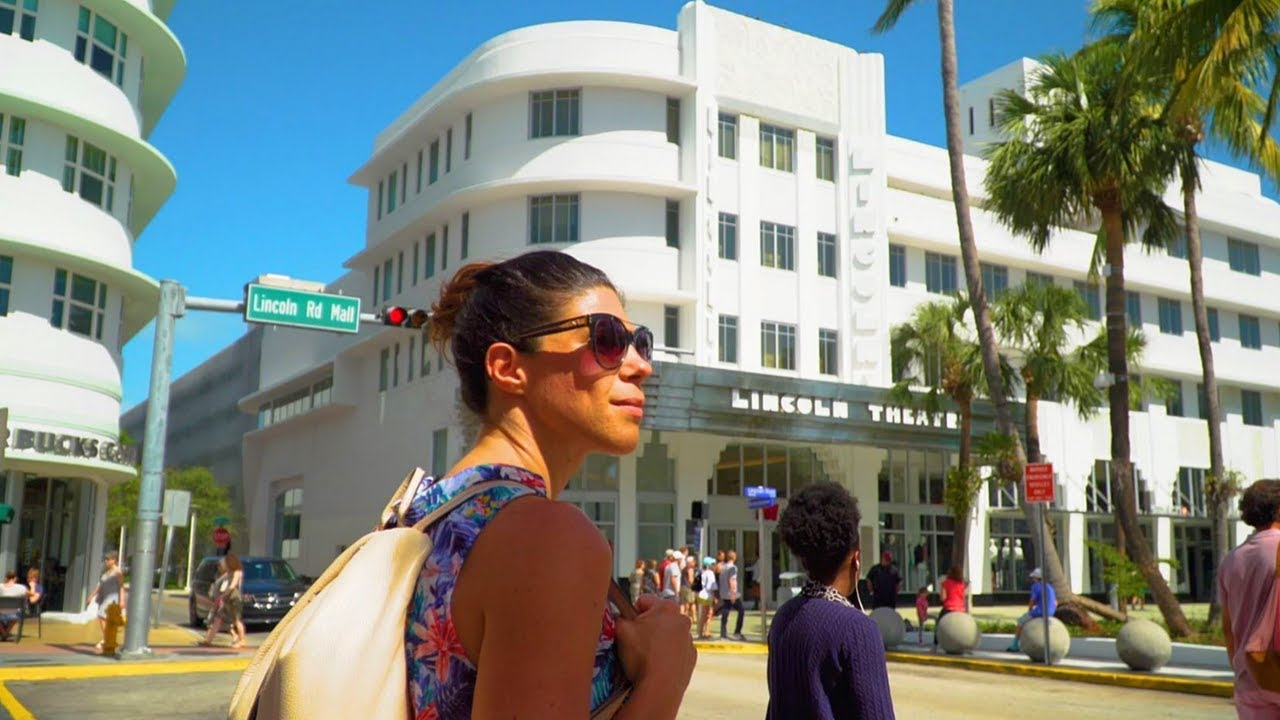 Woman with sunglasses on at Lincoln Road Mall in front of Lincoln Theater