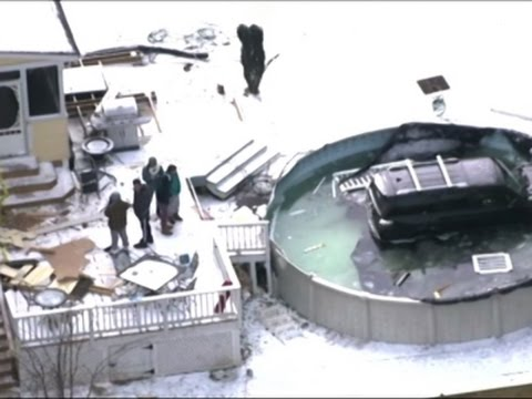 Raw: Car Slides Down Icy Driveway, Lands In Pool