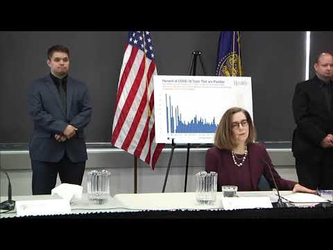 Governor Kate Brown presenting at the June 3rd press conference with a chart and two sign language interpretors in the background
