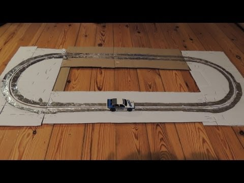 Home made slot car track of cardboard, aluminum foil and staples
